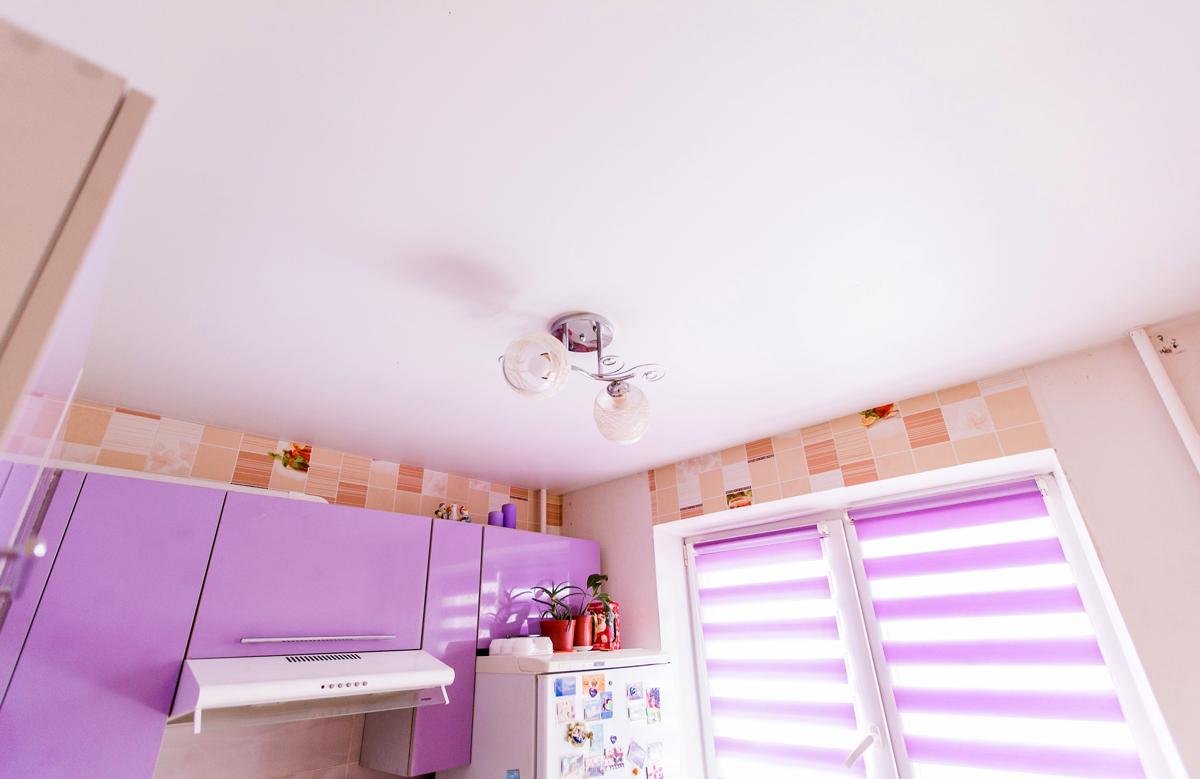 Белый матовый натяжной потолок в кухне с люстрой