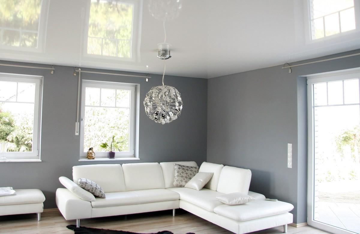Белый глянцевый натяжной потолок с люстрой в гостиной