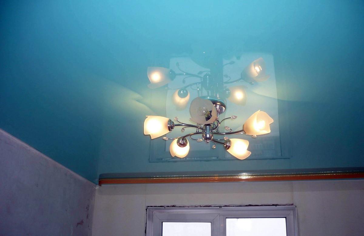 Голубой глянцевый натяжной потолок с люстрой