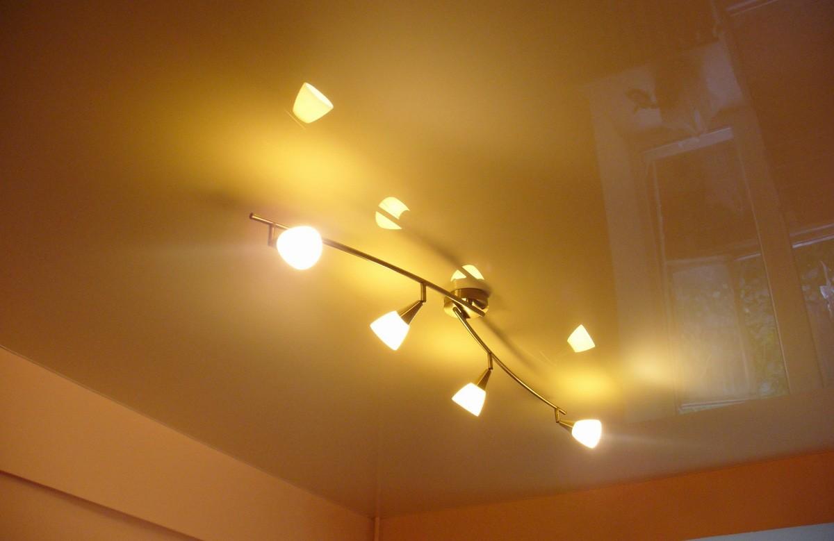 Золотой глянцевый натяжной потолок с люстрой