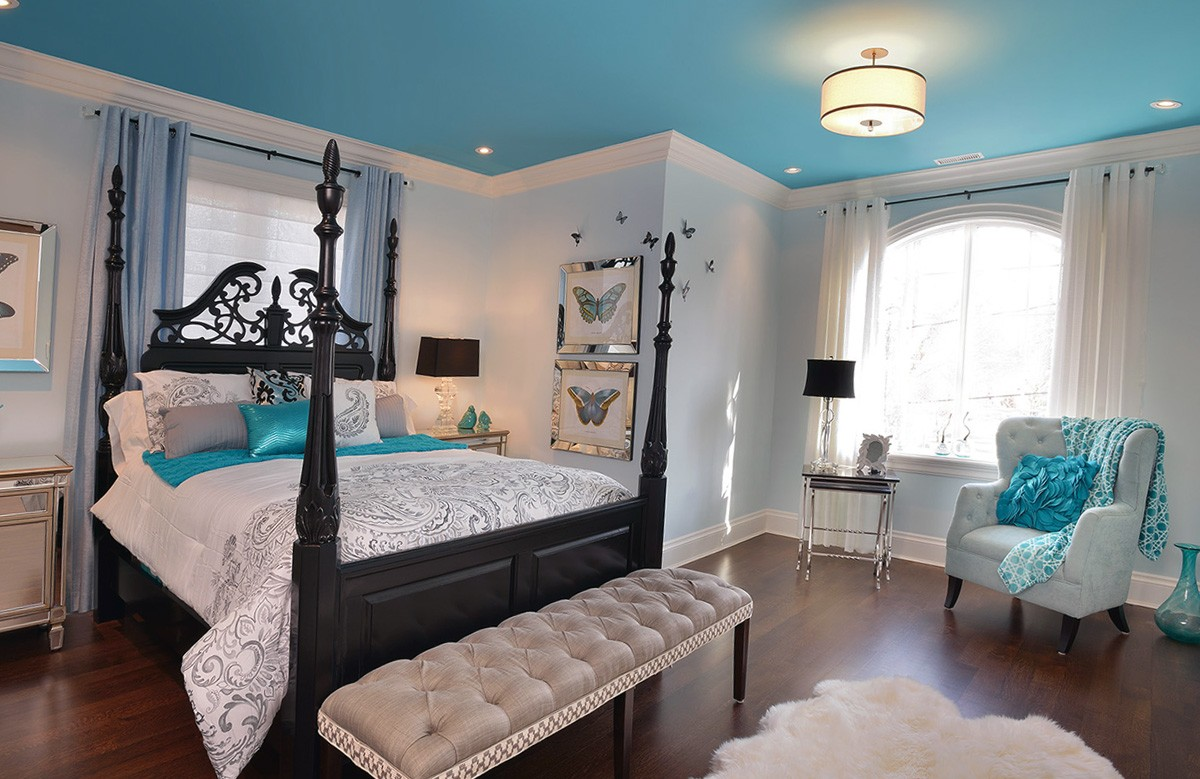 Голубой матовый натяжной потолок в спальне с люстрой и светильниками