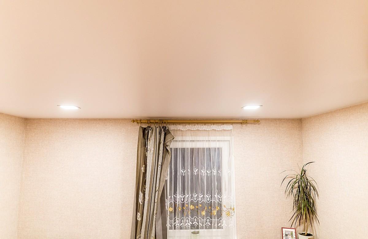 Кремовый матовый натяжной потолок со светильниками в комнате