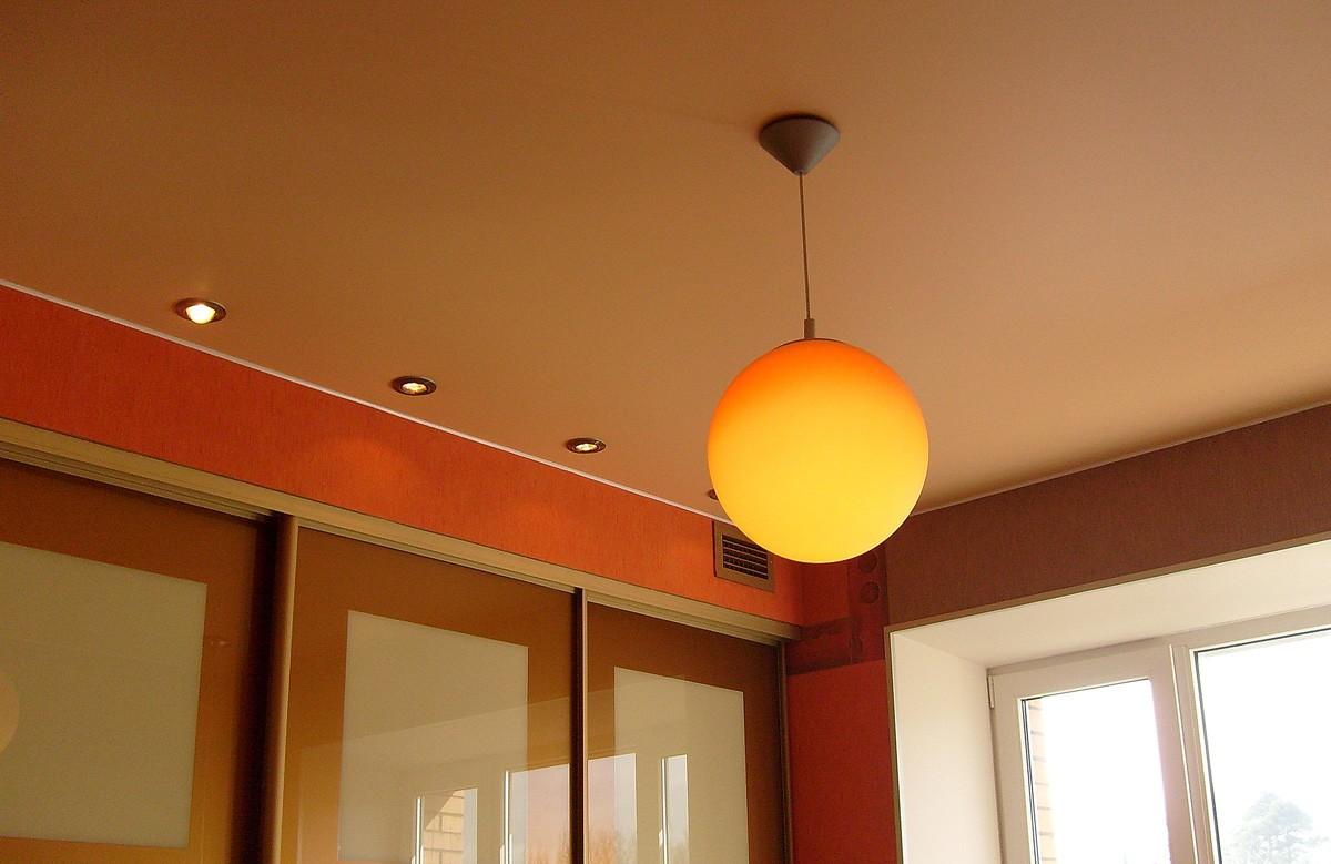 Оранжевый матовый натяжной потолок со светильниками и люстрой