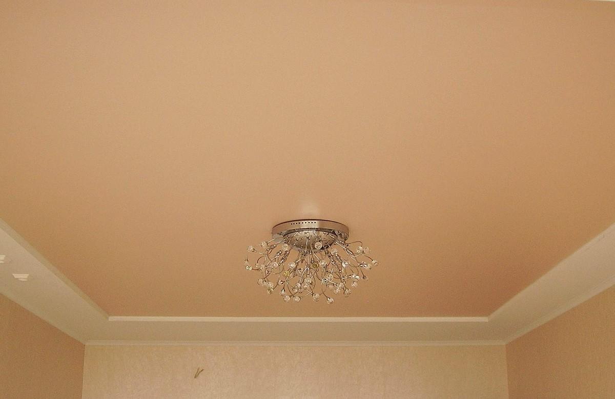 Персиковый матовый натяжной потолок в коробке из гипсокартона с люстрой