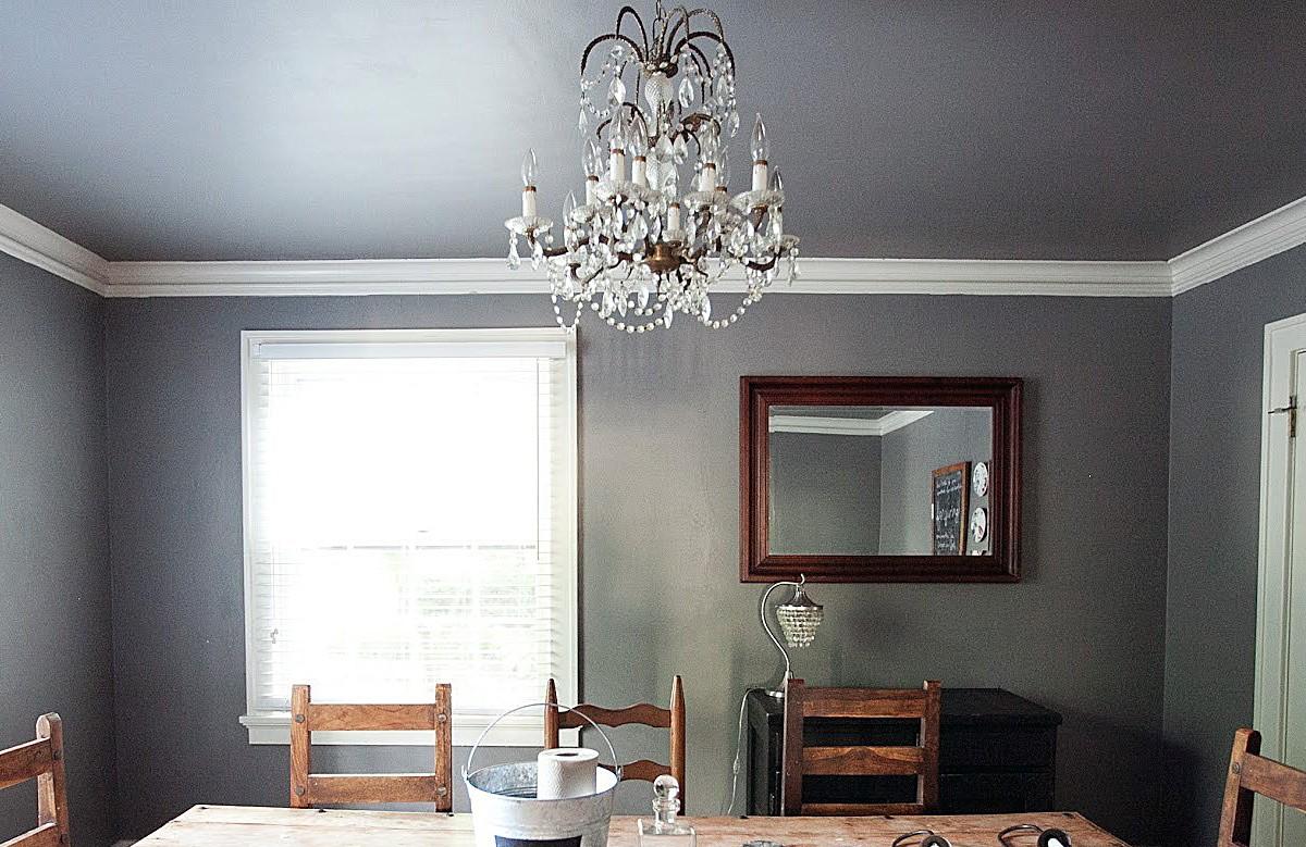 Серый матовый натяжной потолок в столовой с люстрой