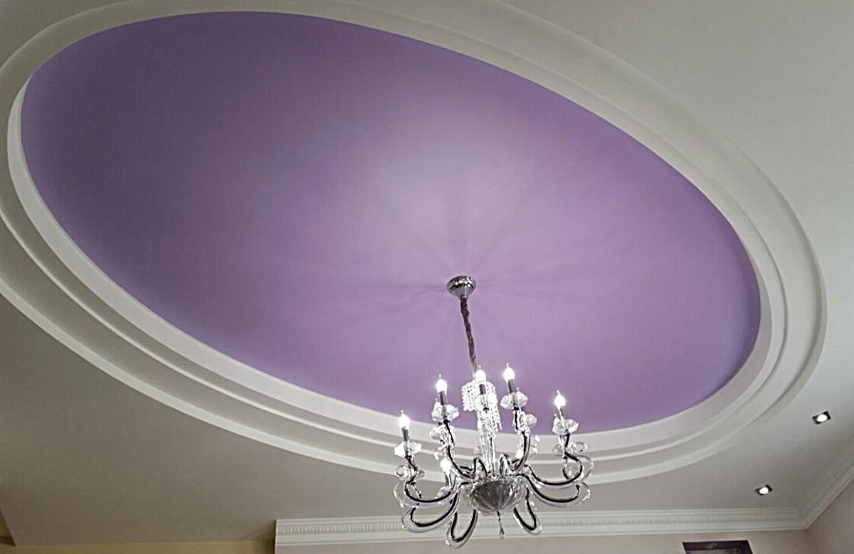 Сиреневый матовый натяжной потолок в гипсокартонном коробе со светильниками и люстрой