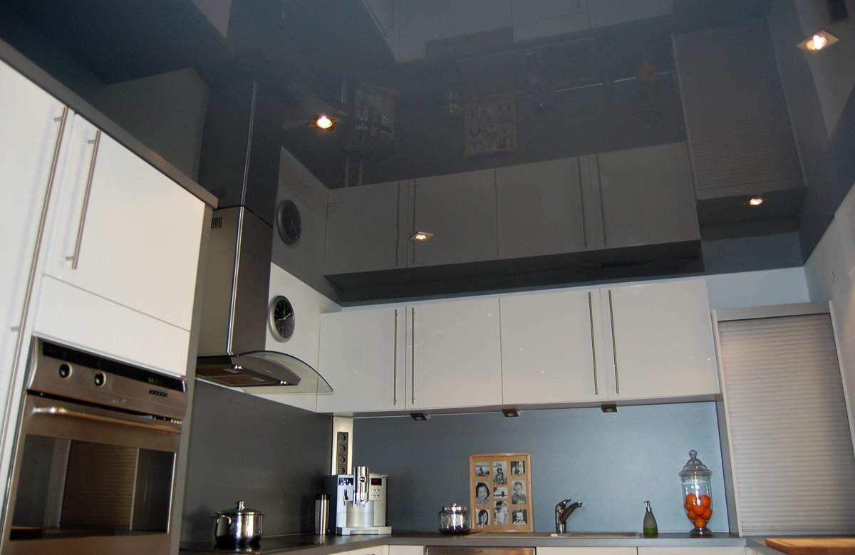 Глянцевый натяжной потолок цвета графита со светильниками в кухне