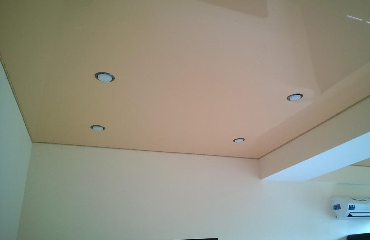 Кремовый глянцевый натяжной потолок с четырьмя светильниками