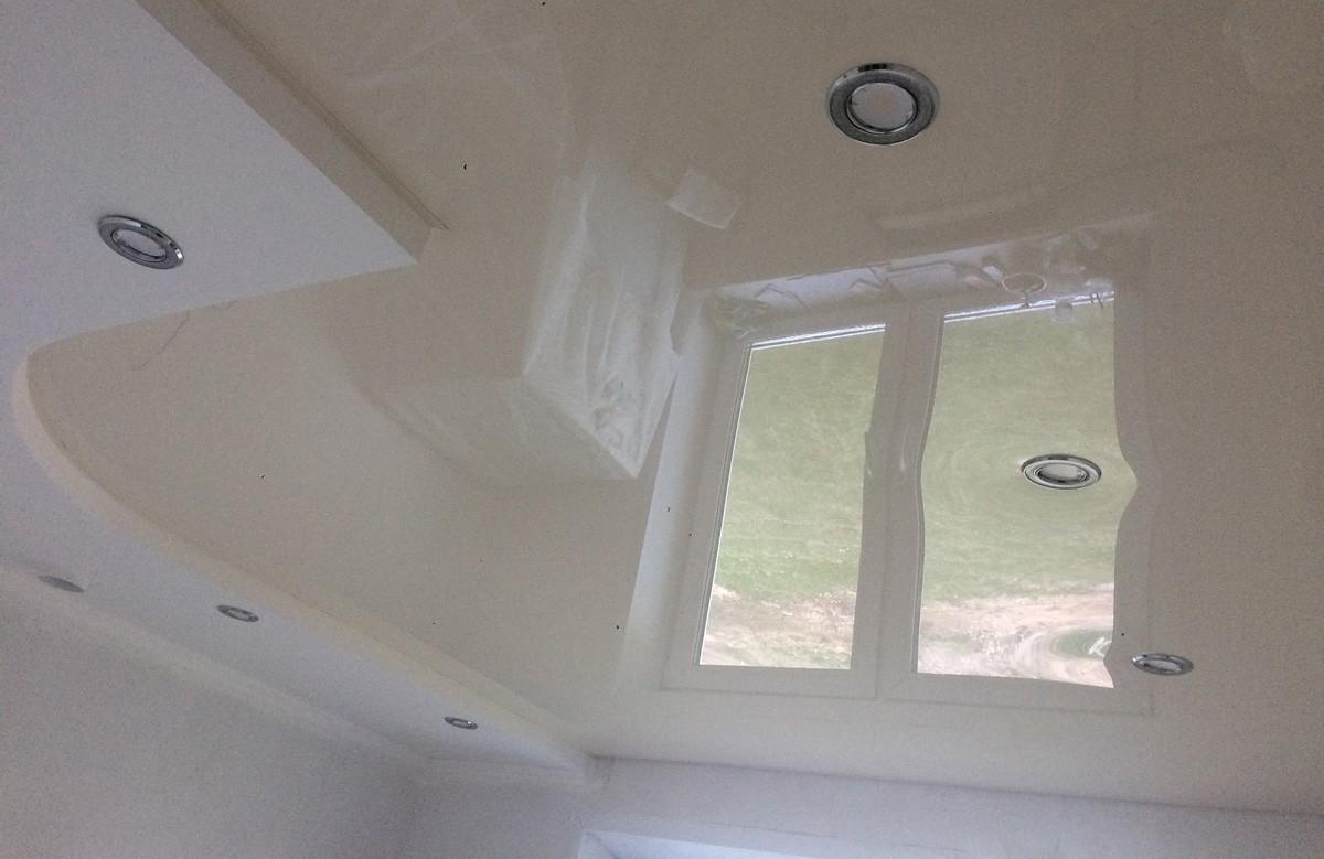 Кремовый глянцевый натяжной потолок со светильниками в гипсокартонном коробе
