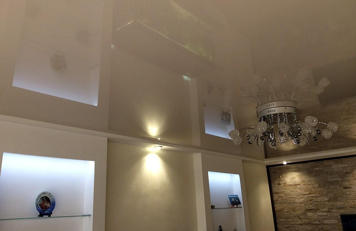 Бежевый глянцевый натяжной потолок с люстрой в коробе из гипсокартона