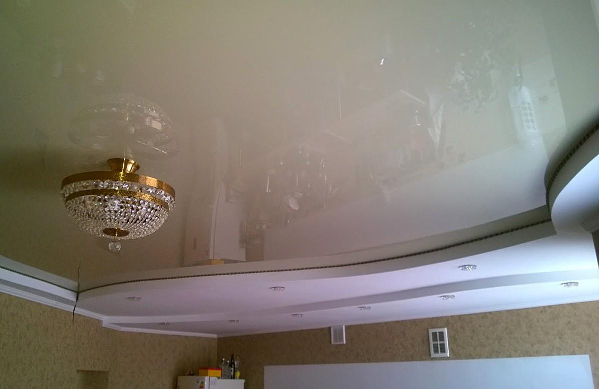 Бежевый глянцевый натяжной потолок с люстрой в гипсокартонном коробе