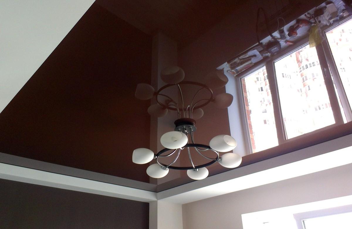 Коричневый глянцевый натяжной потолок с люстрой в коробе из гипсокартона