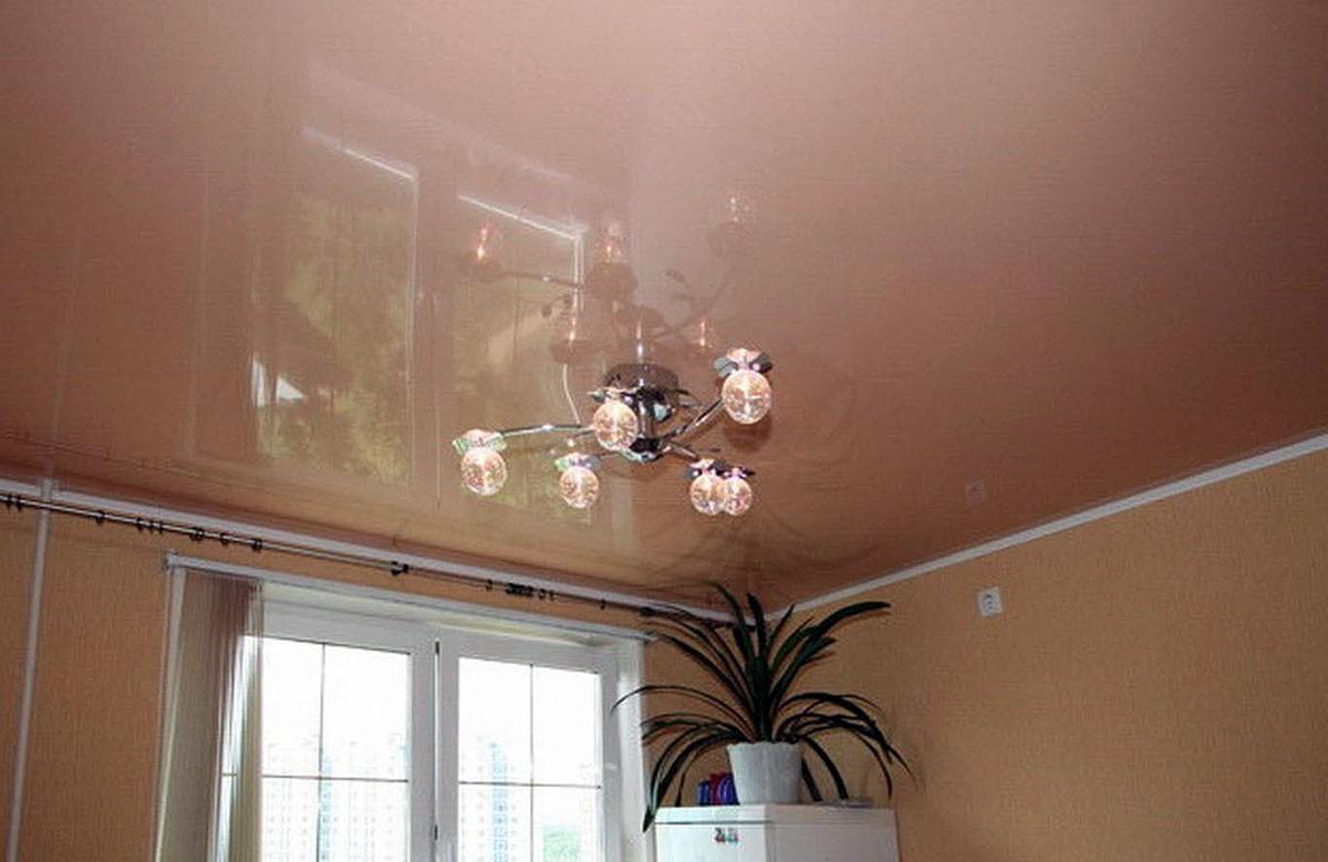 Бежево-розовый глянцевый натяжной потолок с люстрой