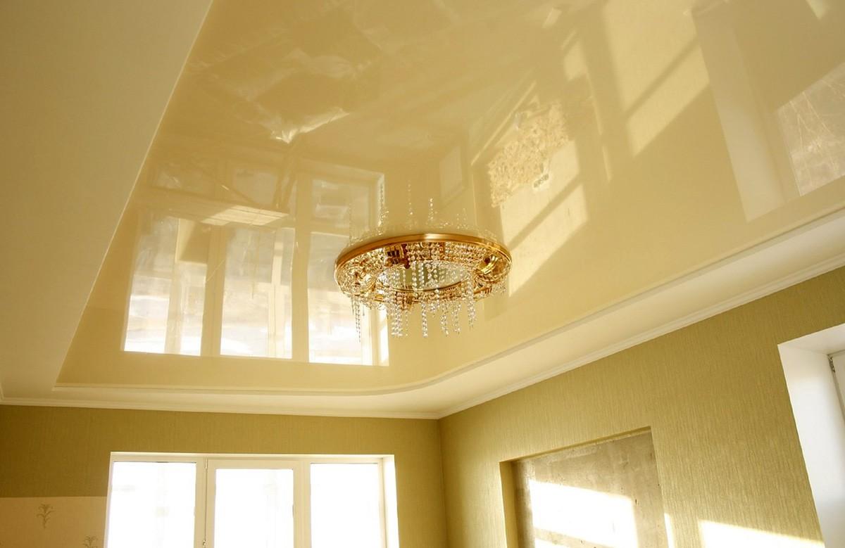 Молочный глянцевый натяжной потолок с люстрой в коробе из гипсокартона