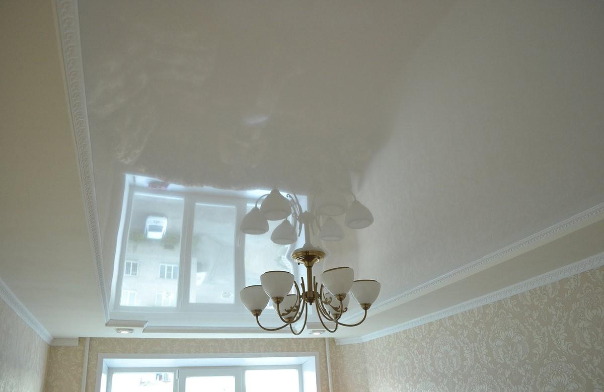 Глянцевый натяжной потолок цвета ванили в коробе из гипсокартона