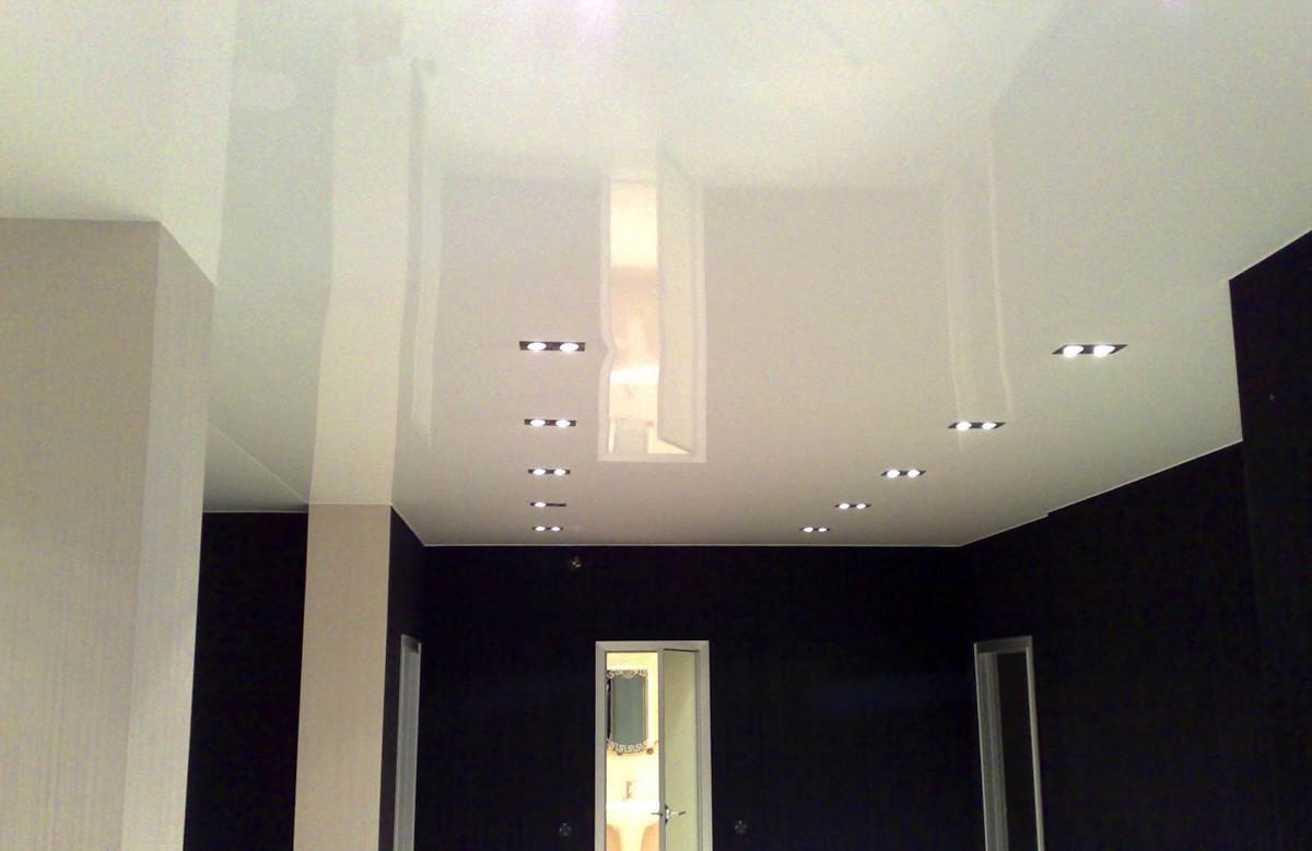 Глянцевый натяжной потолок цвета ванили со светильниками