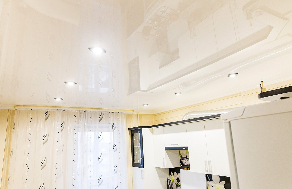 Глянцевый натяжной потолок цвета ванили со светильниками в кухне