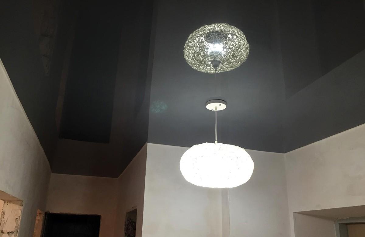 Глянцевый натяжной потолок цвета графита с люстрой