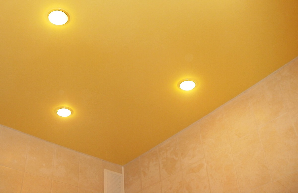 Жёлтый матовый натяжной потолок в ванной с тремя светильниками