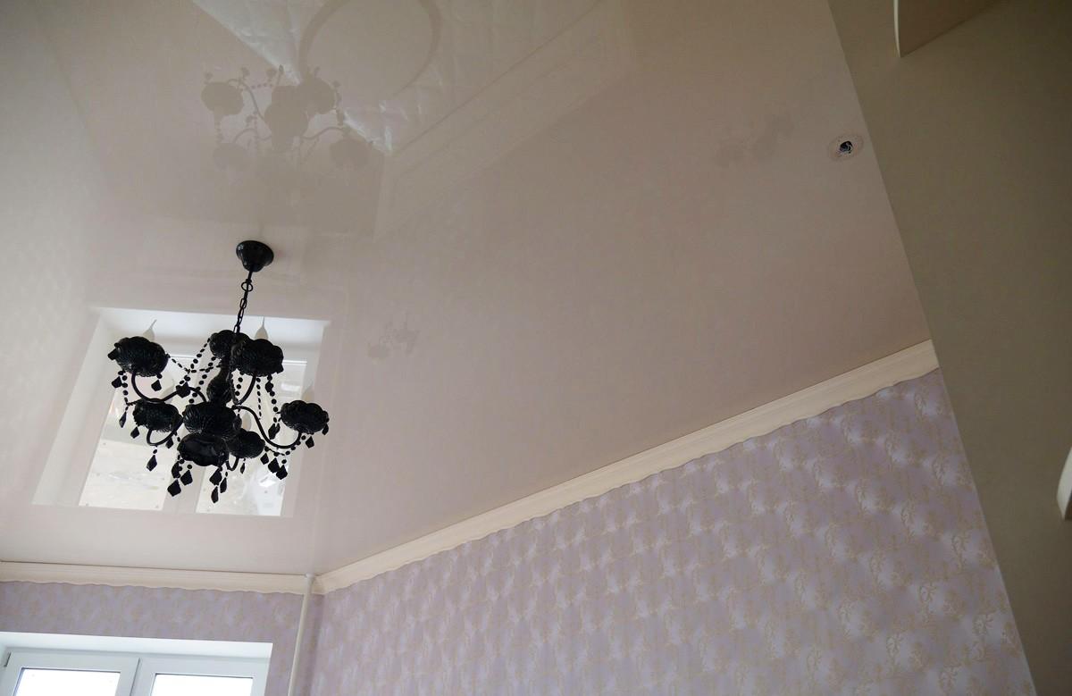 Бежевый глянцевый натяжной потолок с люстрой в комнате